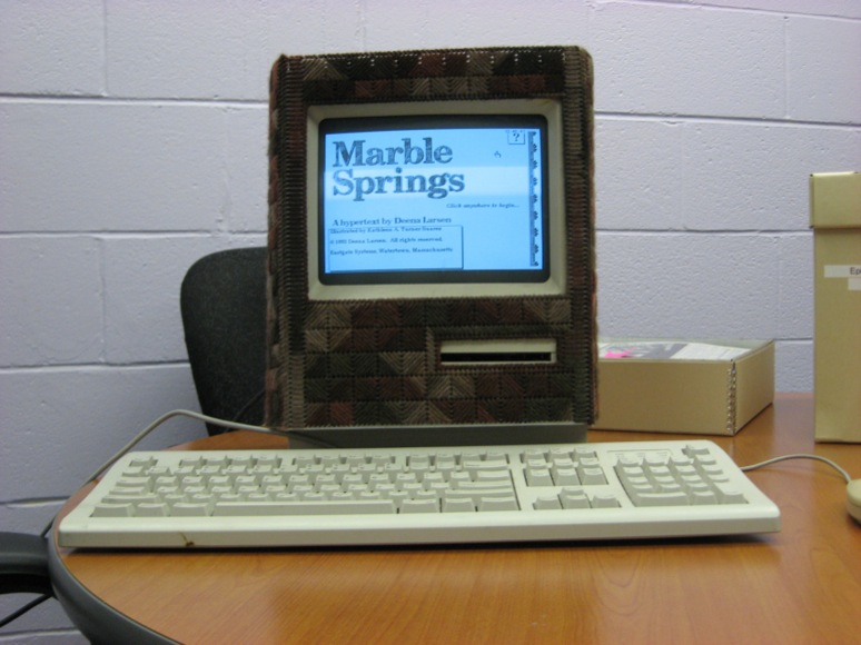 "Photo of Mac Classic wearing ""Mac cozy"" and running Deena Larsen's Marble Springs"