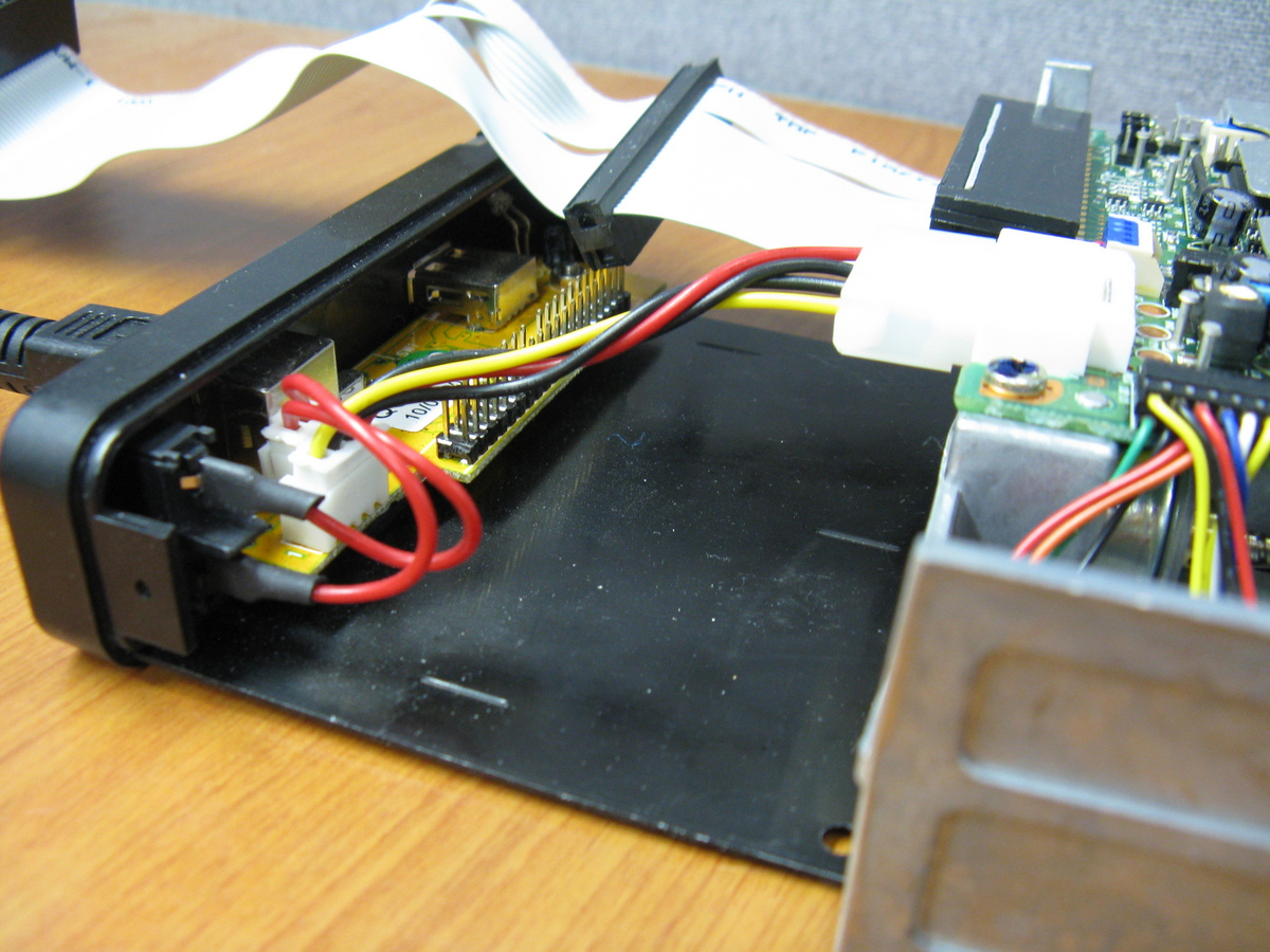 A close-up of attaching the floppy drive to the hard drive sled.
